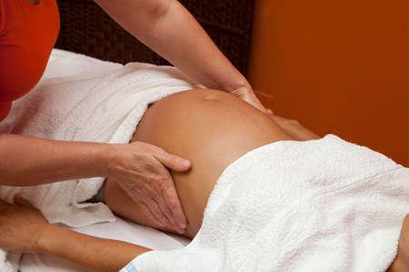massaggio: Giovane donna incinta latina con una bella pelle, essendo avvolto con un asciugamano, sdraiata su un letto e con un rilassante massaggio prenatale, varie tecniche