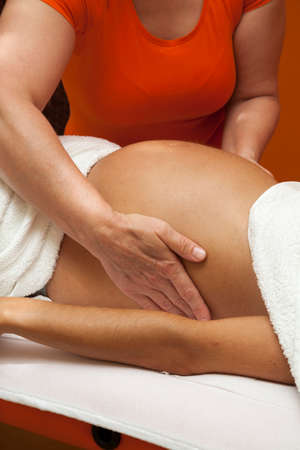 Pregnant young latina woman with beautiful skin, being wrapped with a towel, lying on a bed and having a relaxing prenatal massage, various techniques photo