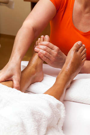 Woman receiving a leg and foot massage while lying on a towel\ in a awarded health massage center, series of various\ techniques