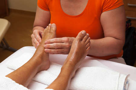 Woman receiving a leg and foot massage while lying on a towel in a awarded health massage center, series of various techniques  photo