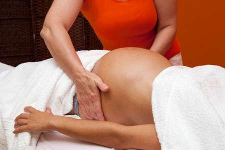 mujeres embarazadas: Mujer latina joven embarazada con una piel hermosa, est� envuelto con una toalla, acostado en una cama y con un relajante masaje prenatal, diversas t�cnicas