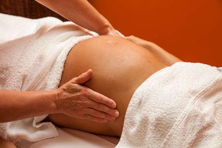 massage b�b�: Jeune femme enceinte latina avec une belle peau, �tant envelopp� dans une serviette, couch� sur un lit et d'un massage pr�natal de d�tente, diverses techniques Banque d'images