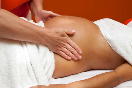 Pregnant young latina woman with beautiful skin, being wrapped with a towel, lying on a bed and having a relaxing prenatal massage, various techniques Stock Photo