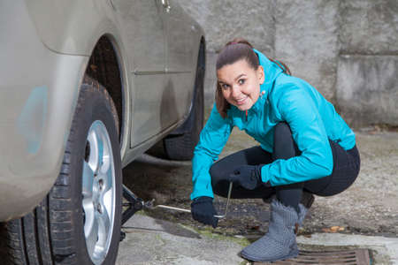 Cute young woman driver loosening nuts on car wheel for a tire change  photo