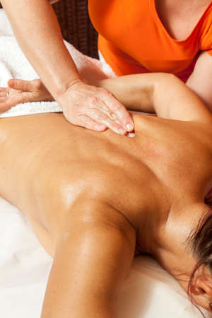 Woman receiving a professional therapeutic body, leg and foot massage and lymphatic drainage, while lying on a towel in a awarded health massage center,  demonstration of various techniques