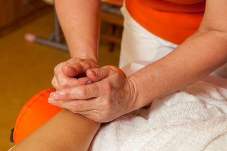 Woman receiving a professional therapeutic body, leg and foot massage and lymphatic drainage, while lying on a towel in a awarded health massage center,  demonstration of various techniques  photo