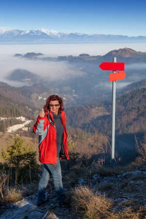 Cute smiling hiker woman at mountain top summit giving success thumbs up sign, standing by the red guidepost, space for text photo