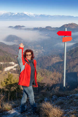 Cute smiling hiker woman at mountain top summit waving hello, standing by the red guidepost, space for text photo