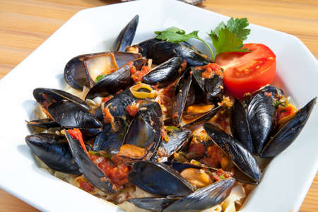 Pasta with Mediterranean mussels in tomato sauce with fresh herbs