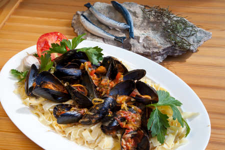 Pasta with Mediterranean mussels in tomato sauce with fresh herbs, decorated with sardines sculptures