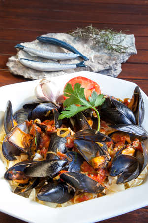 mussle: Pasta with Mediterranean mussels in tomato sauce with fresh herbs, decorated with sardines sculptures