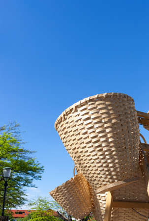 Handmade traditional straw wicker baskets on sunny market,   against blue sky