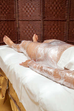 Mid aged female body being wrapped around with foil to reduce fat