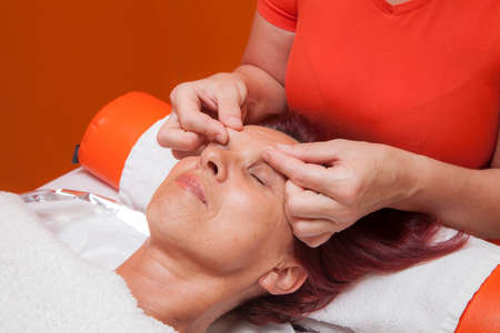 Cute mid aged woman receiving a professional therapeutic facial massage and lymphatic drainage, while lying on a towel in a award-winning health massage center, series of various techniques  photo