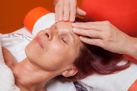 lymphatic drainage: Cute mid aged woman receiving a professional therapeutic facial massage and lymphatic drainage, while lying on a towel in a award-winning health massage center, series of various techniques