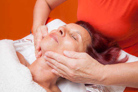 Cute mid aged woman receiving a professional therapeutic facial massage and lymphatic drainage, while lying on a towel in a award-winning health massage center, series of various techniques