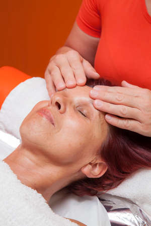 lymphatic drainage therapy: Cute mid aged woman receiving a professional therapeutic facial massage and lymphatic drainage, while lying on a towel in a award-winning health massage center, series of various techniques