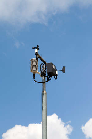 anemometer: Weather station, anemometer measuring wind speed and direction, against a blue, cloudy sky