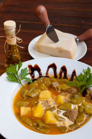 Portion of traditional Mediterranean beef stew, goulasch,  decorated with parsley and superior balsamic vinegar and served with organic parmesan cheese and virgin olive oil photo