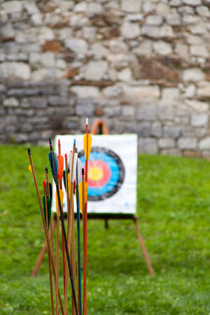 Arrows and target archery in field  Colorful Arrows and target archery in field against castle walls, selective focus Stock Photo