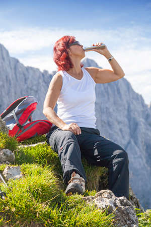 Cute middle aged woman hiker with hip flask, pauses at the top of a high mountain in Alps  photo