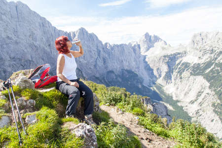 Cute middle aged woman hiker with hip flask, pauses at the top of a high mountain in Alps