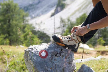 Cute female hiker tying boot laces on rock with signpost, high in the mountains photo