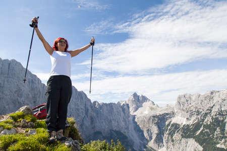 Gelukkige vrouw van middelbare leeftijd opgetogen met opgeheven armen omhoog boven haar hoofd in de viering van de hoge berg top tijdens wandelen te hebben bereikt
