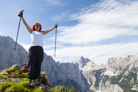 Happy middle aged woman standing elated with arms raised up above her head in celebration of having reached high mountain top during hiking Stock Photo