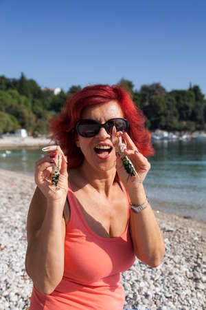 age 40 45 years: Cute middle-aged woman enjoying fresh, raw Mediterranean scampi, outside on the sunny autumn beach, high resolution photo Stock Photo
