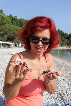 45 50 years: Cute middle-aged woman enjoying fresh, raw Mediterranean scampi, outside on the sunny autumn beach, high resolution photo Stock Photo