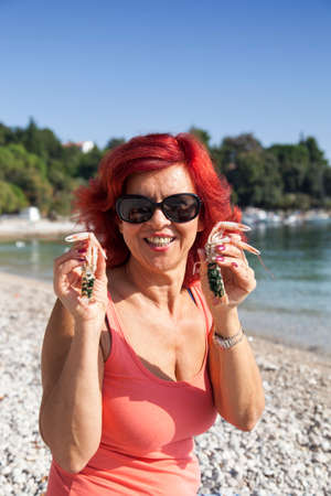 age 40 45 years: Cute middle-aged woman enjoying fresh, raw Mediterranean scampi, outside on the sunny autumn beach Stock Photo