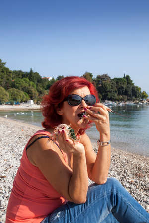 45 50 years: Cute middle-aged woman enjoying fresh, raw Mediterranean scampi, outside on the sunny autumn beach Stock Photo