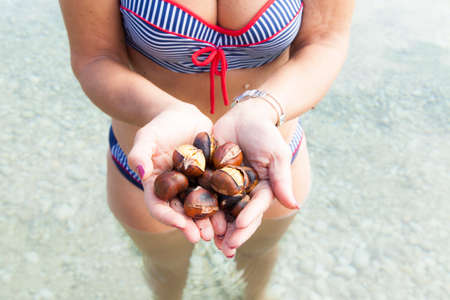 Pretty middle aged woman with roasted chestnuts on the sunny beach, whilst standing in sea, wet skin with goosebumps photo