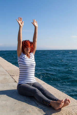joga: Performing Joga on windy day. Cute woman meditating, performing joga on sea coast, windy sunny day, high, rough sea in the background