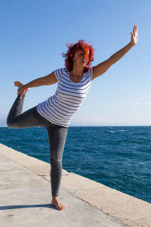 Performing Joga on windy day. Cute woman meditating, performing joga on sea coast, windy sunny day, high, rough sea in the background photo