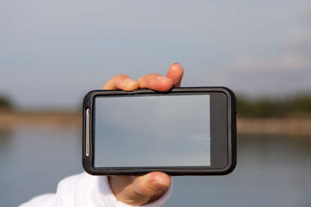 Hand showing smart mobile phone with blank screen, beach background photo