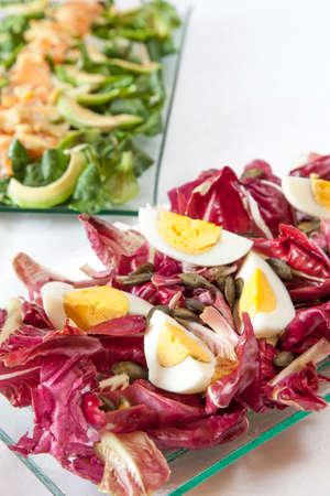 cornsalad: Salads, Hard-boiled eggs with organic red chicory, salmon salad with avocado and fresh organic  Corn salad, fennel and pignoli, with mustard sauce, selective focus