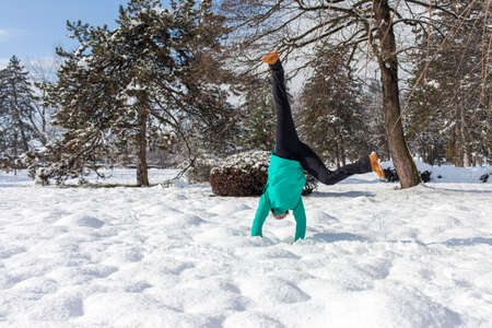 winter photos: Cute young woman performing cartwheel, outdoor on a sunny winter day, Series of high resolution photos Stock Photo