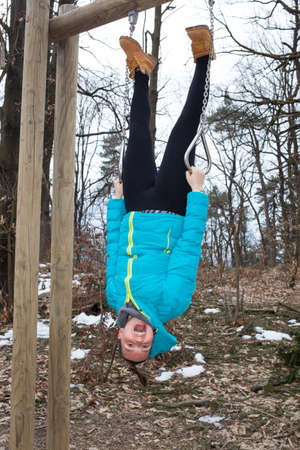 pull up: A young sporty woman is upside down dangling from a pull up bar in the park Stock Photo