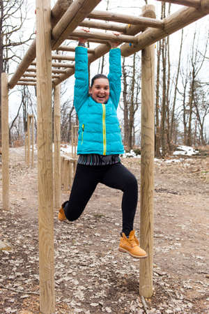 hang body: Pretty smiling girl training on fitness brachiation ladder or monkey bars obstacle, hanging swinging from rung to rung as part of crossfit workout routine