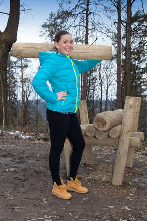 jungle gyms: Young athletic fitness woman lifting a heavy trunk out at outdoor gym