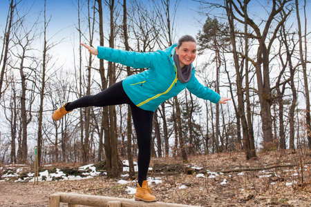 jungle gyms: Young athletic fitness woman working out at outdoor gym on balance beam Stock Photo