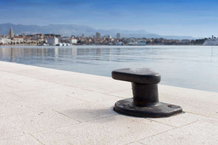 Metal mooring bollard on the dock of concrete harbor pier, against coastal town Stock Photo