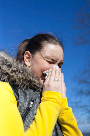 Pretty girl sneezing outdoors, on sunny windy day, against beautifull blue sky