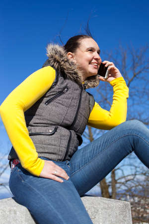 windy day: Pretty smilling young woman using smart cellphone outdoors on sunny  windy day, against dark blue sky, space for text Stock Photo