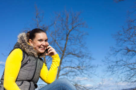 blurr: Pretty smilling young woman using smart cellphone outdoors on sunny  windy day, against dark blue sky, space for text Stock Photo
