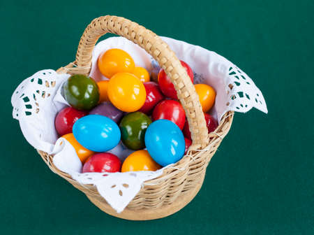 Colorful Easter eggs inside straw wicker basket on green background photo