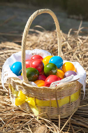 Colorful Easter eggs inside straw wicker basket on straw background photo