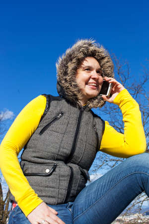 windy day: Pretty smiling young woman using smart cellphone outdoors on sunny windy day against dark blue sky